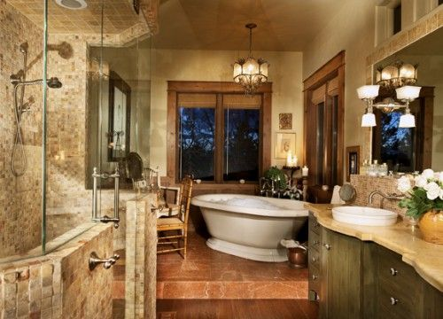"""This space is a mix of textures that I love. The floor in front of the vanity is hand scraped walnut in random widths. The floor of the """"princess platform"""" where the tub is located is a honed marble, so it has a matte finish. The shower is covered in 1""""x1"""" Jerusalem stone, which is a limestone. The countertop is honed limestone with a marble shelf behind it of tiny polished mosaic. The space is very soothing with calm, warm colors."""