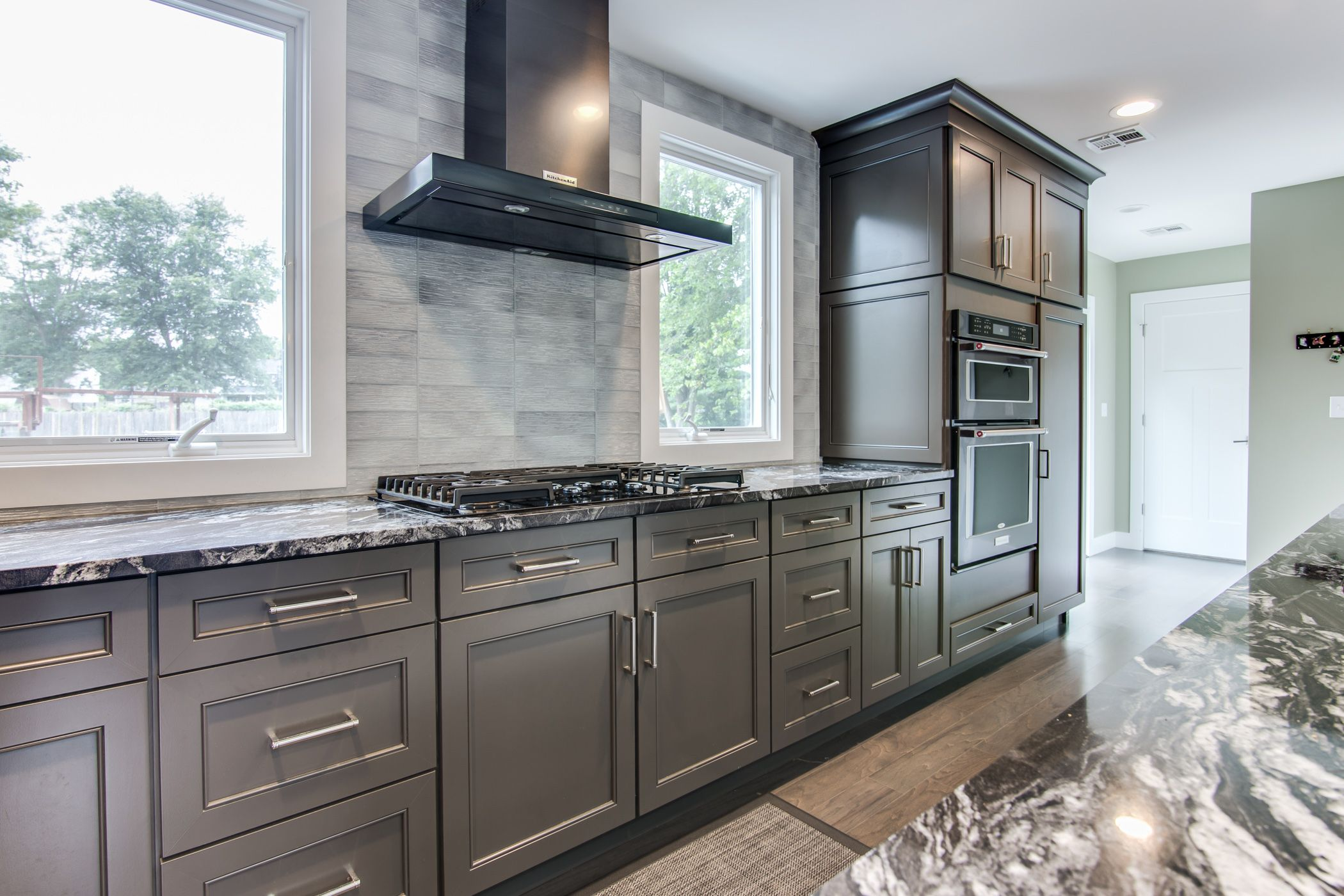 Black Stainless Steel Kitchenaid Rangehood In Between Windows In A