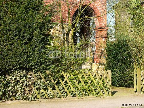 Alter Jägerzaun mit Gartentür vor einer alten Villa in