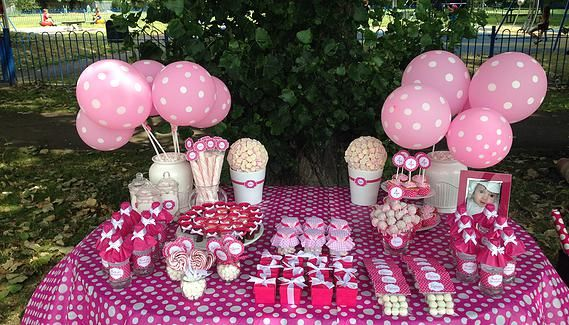 Pink polka dot table decoration (cake is missing)