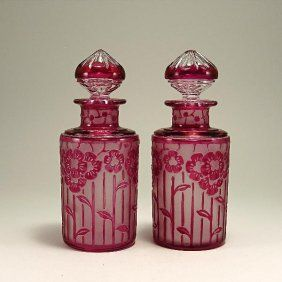 1920s Cristalleries de Nancy pair of perfume bottles in cranberry cased crystal cut to clear, floral pattern. Signed. 6 1/4 in.
