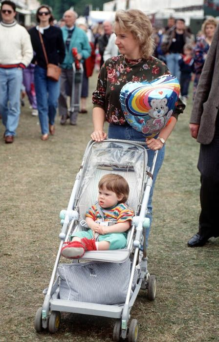 Princess Eugenie is pushed around the grounds at the Royal Windsor Horse Show in Berkshire by her royal nanny, Alison Wardley, 1991.