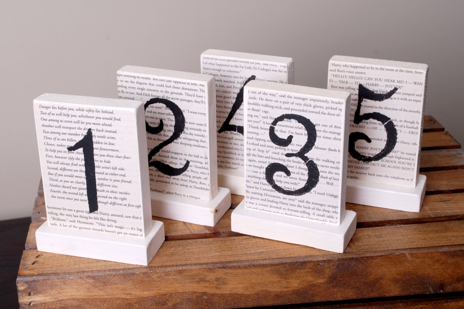 Book Page/Storybook Wedding Table Numbers 1-20  For the ultimate wizard fan or dedicated bookworm!! This listing is for 5 table numbers.  Include this classy addition in your ultimate wizard wedding! Or include these table numbers to create the perfect Storybook Wedding!  These table numbers are all wood that stand alone, no propping needed. Each table number is painted in off white. Both sides are embellished with actual book pages and then stenciled with a number on one or both sides. ...