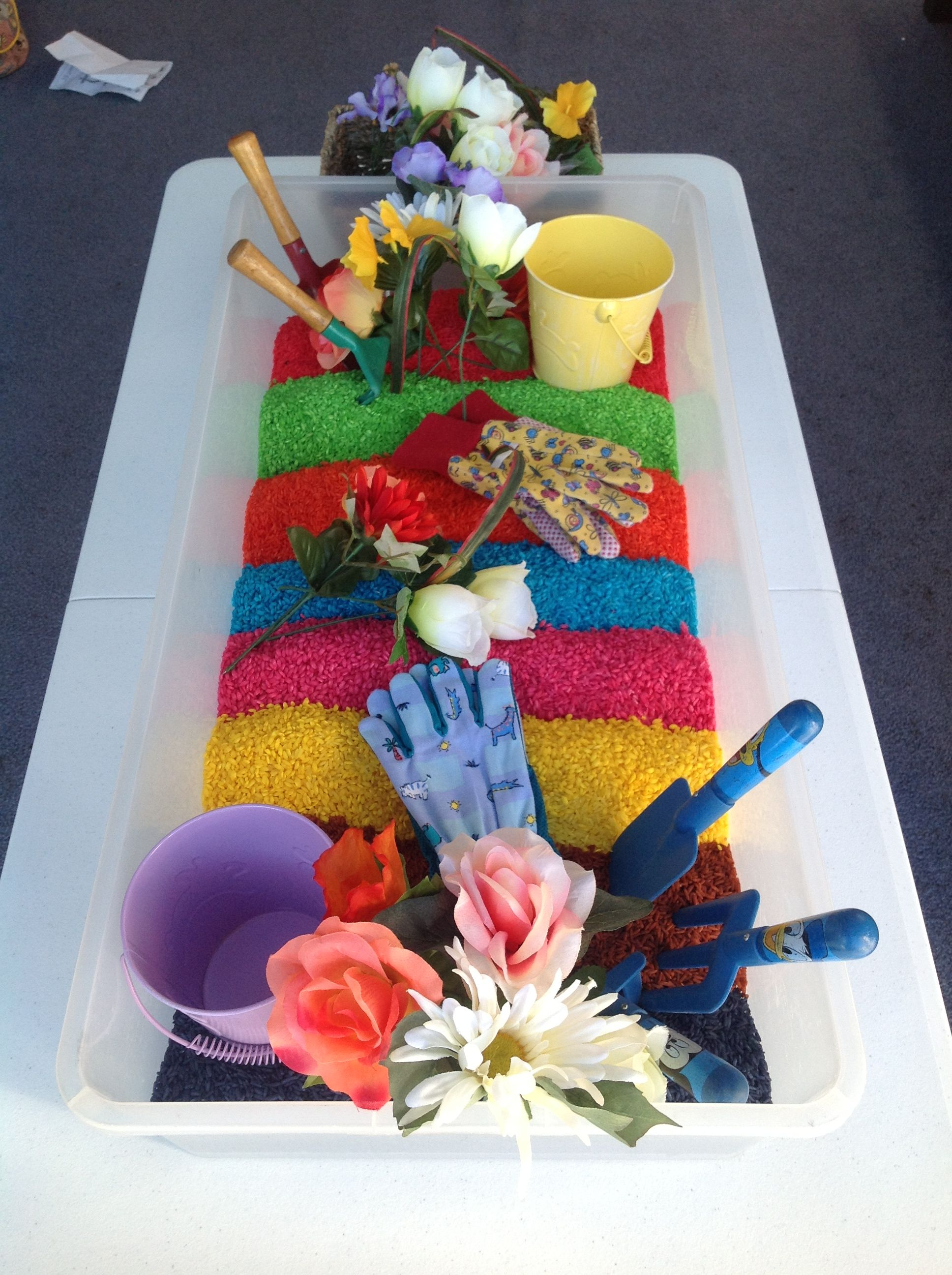Invitation to Create - Rainbow rice and gardening tools.