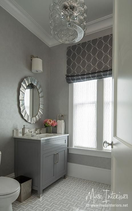 Gray powder room features a gray vanity topped with gray