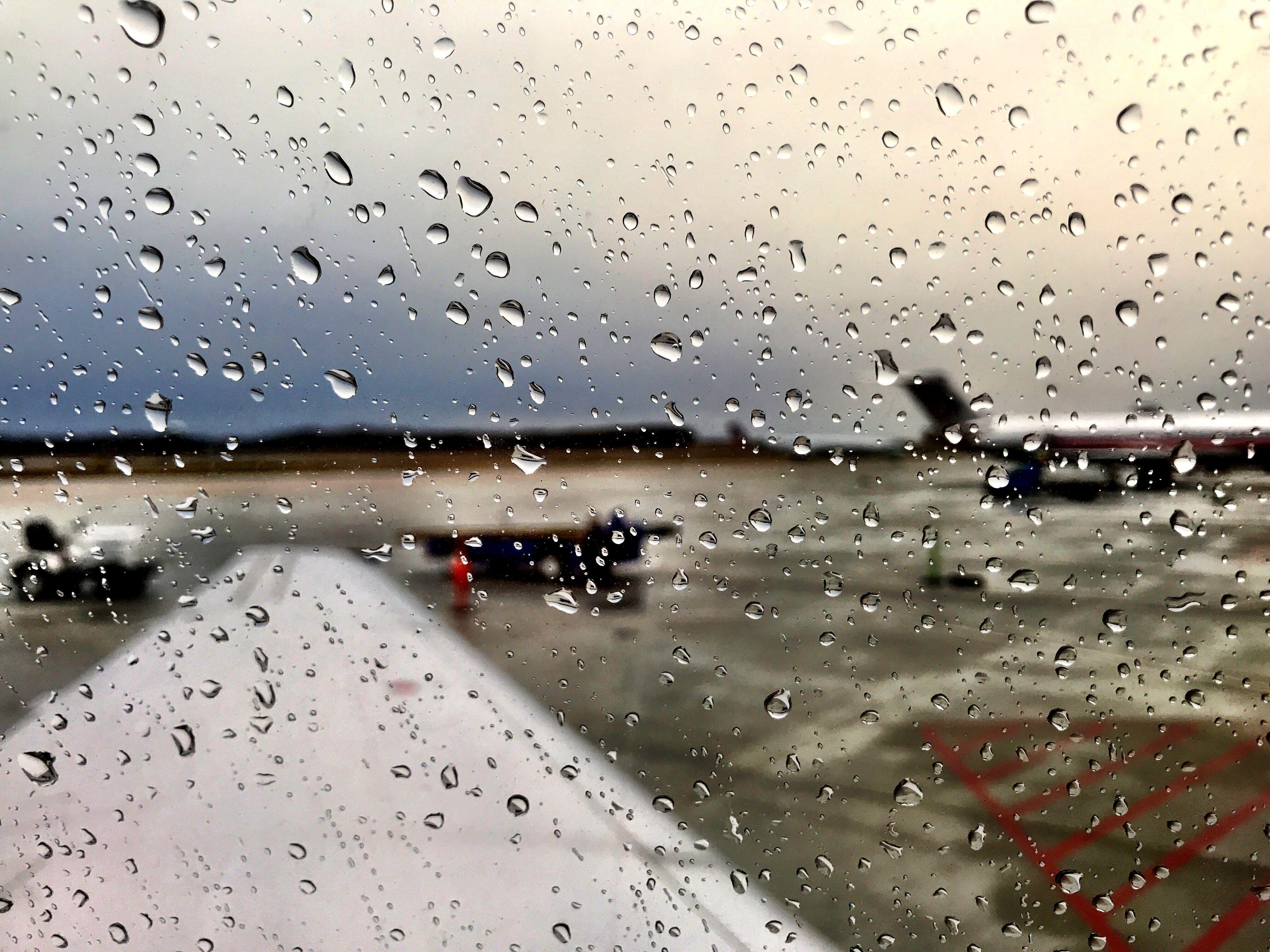 Raindrops on plane window. Rainy Monday. Plane window