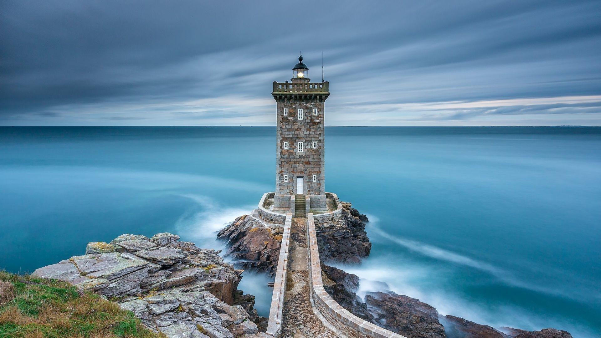 фото маяка на скале с видом в море