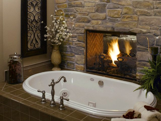 Fireplace in wall between bedroom and built in tub in ...