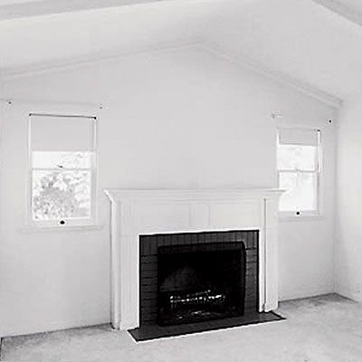 living room with a fireplace that has two narrow windows on each ...