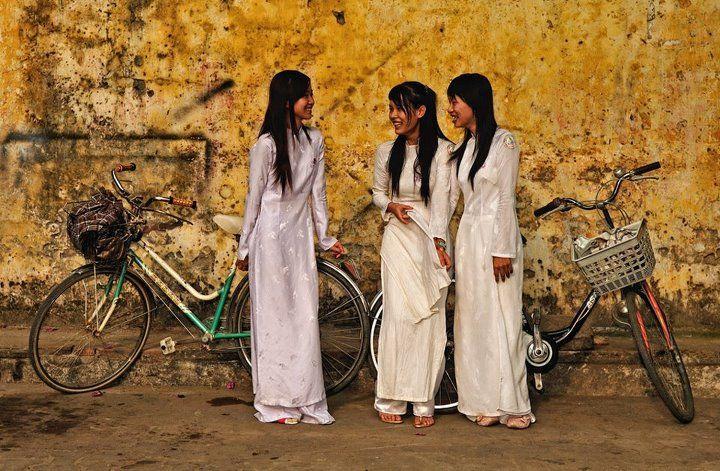 Tres chicas de Hoi An se dejan fotografiar camino del colegio. Hoi An es una pequeña ciudad en la costa del mar de la China Meridional, en Vietnam central, que cuenta con aproximadamente 88.000 habitantes. Fotografía de Malcolm Fackender.