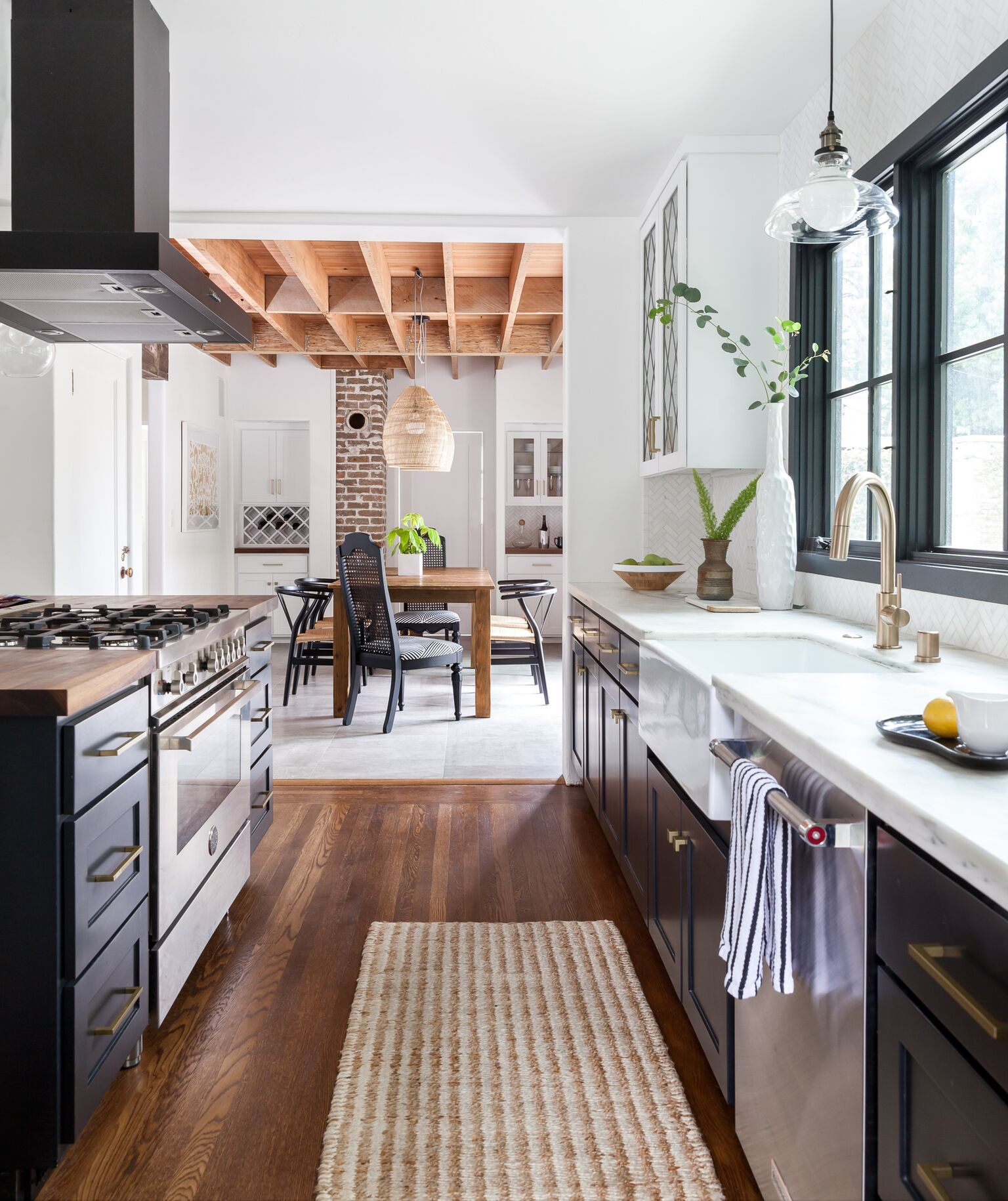 Kitchen With Black Cabinets White Marble Countertops And An