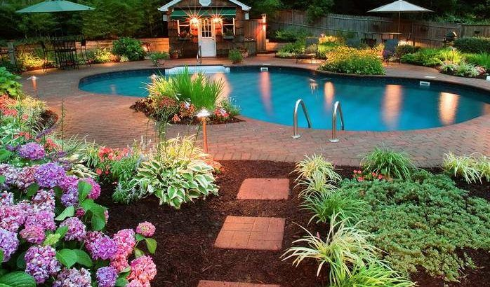 night view overlooking a swimming pool and garden of a