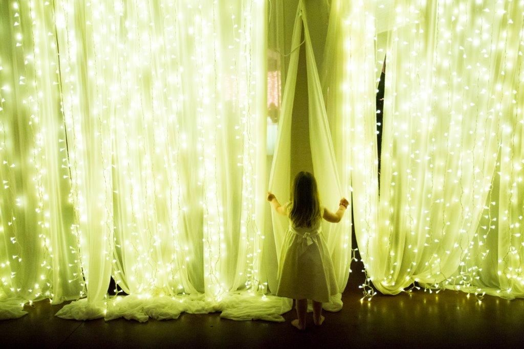 A beautiful alternative to star cloth - chiffon curtains with fairy lights to create a stunning backdrop for our wedding dinner.