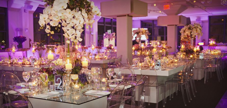 Custom made dinner tables for a Winter Wonderland themed bat mitzvah included floating candles on water and flowers in different shades of purple.