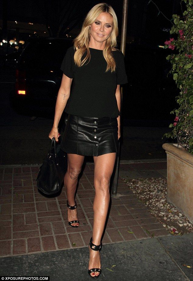 Heidi Klum showcases her slender legs in a black leather mini ...