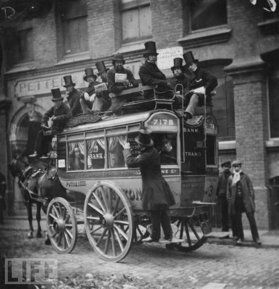 Crowded Bus Ride in London, 1865. Victorian horse-drawn 'bus' car filled with men, including a group in top hats seated on top of the coach.