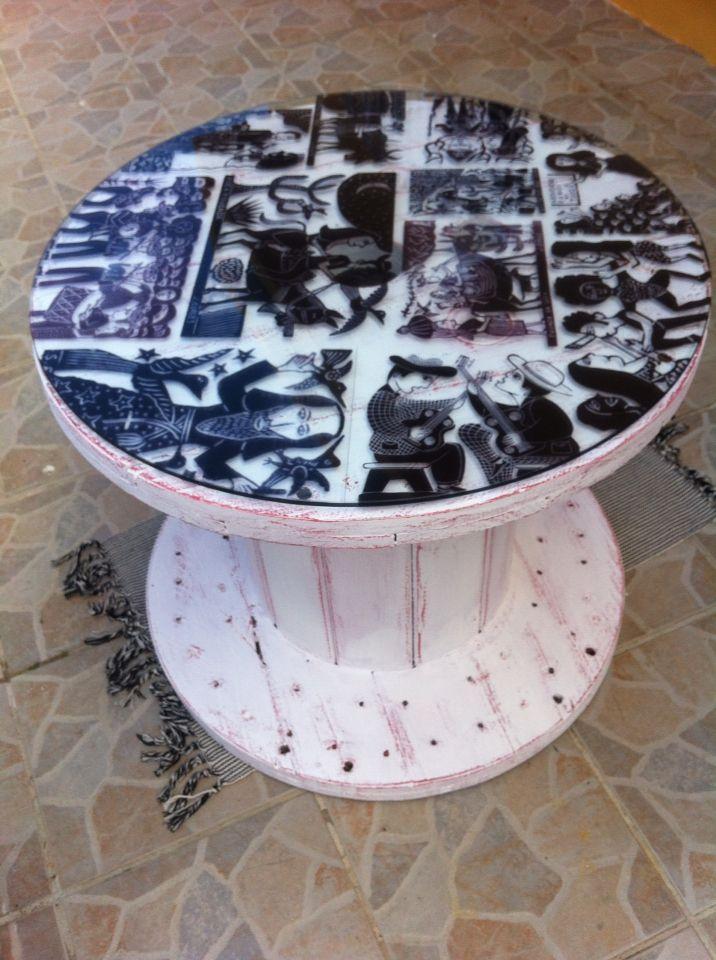 Mesinha/centro. 0,65 cm de diâmetro. 0,57 cm de altura. Pintura em pátina provençal branca e vermelha. Rodinhas deslizantes e com travas. Tampo de vidro com estampas de xilogravuras de cordel.