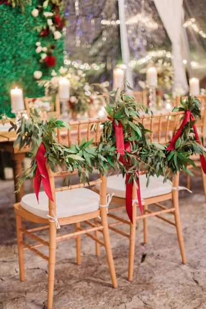 Loving this draped greenery and red accented chair treatment for Rachel and Gabe's holiday wedding! Photographed by Stephanie Hunter Photography. // Rentals by Premiere Events. #bridesofaustin #wedding #chairs