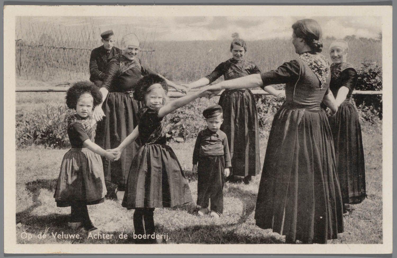 Vier jongevrouwen, twee meisjes en een jongen spelende een kringspel. Op de achtergrond kijkt een man toe. Allen zijn gekleed in Veluwse streekdracht. na 1905 #Veluwe #Gelderland #oudedracht