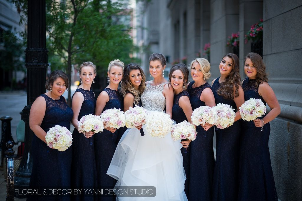 Bride and bridesmaids hold their elegant  bridal bouquets made up of white and light pink ivory roses and Dendrobium Orchids.