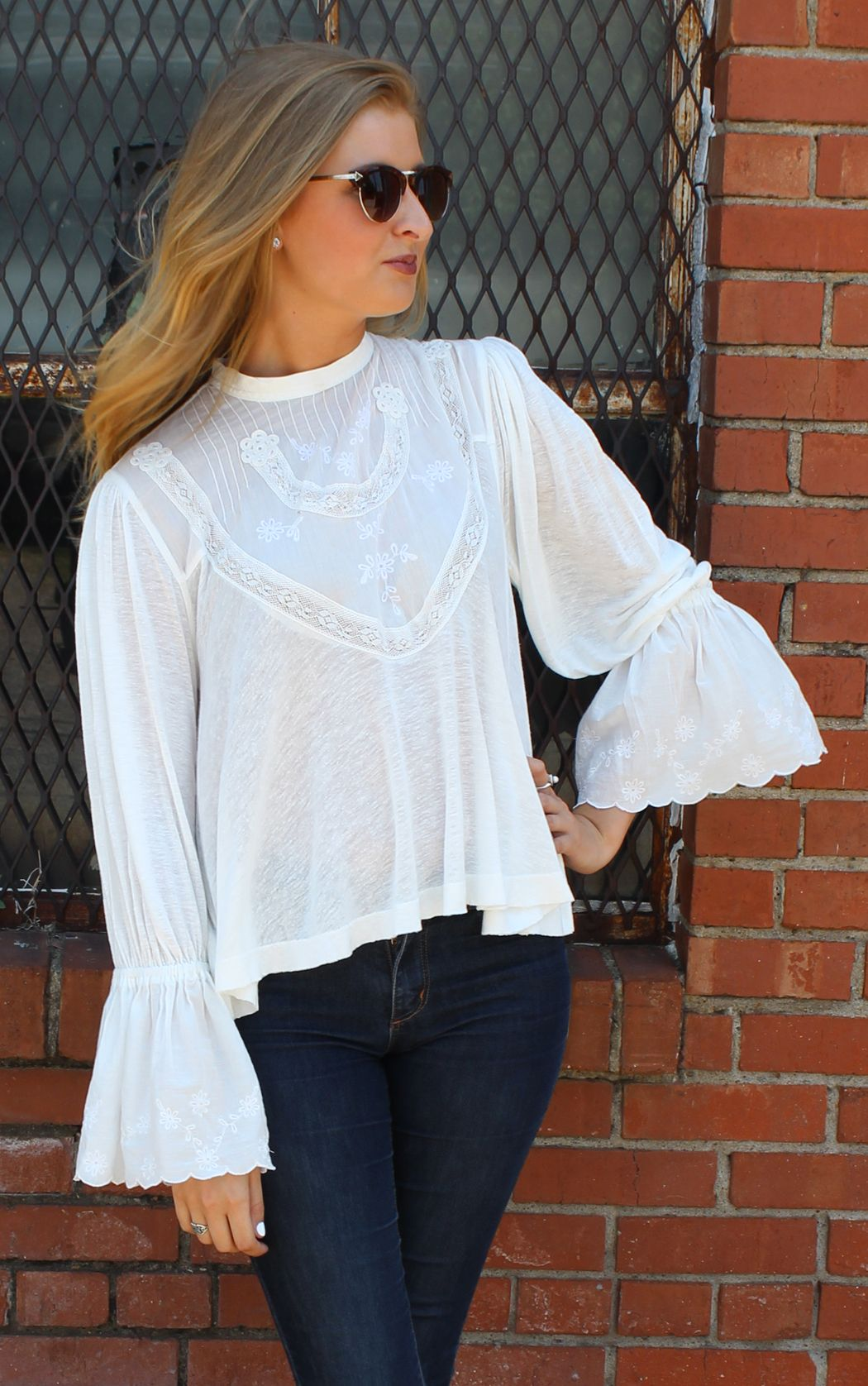 f84ad1531a3116 Femme Fatale Top by Free People White, lace detailing, flared at bottom of  sleeves, buttoned in back with a split very small high low hem.