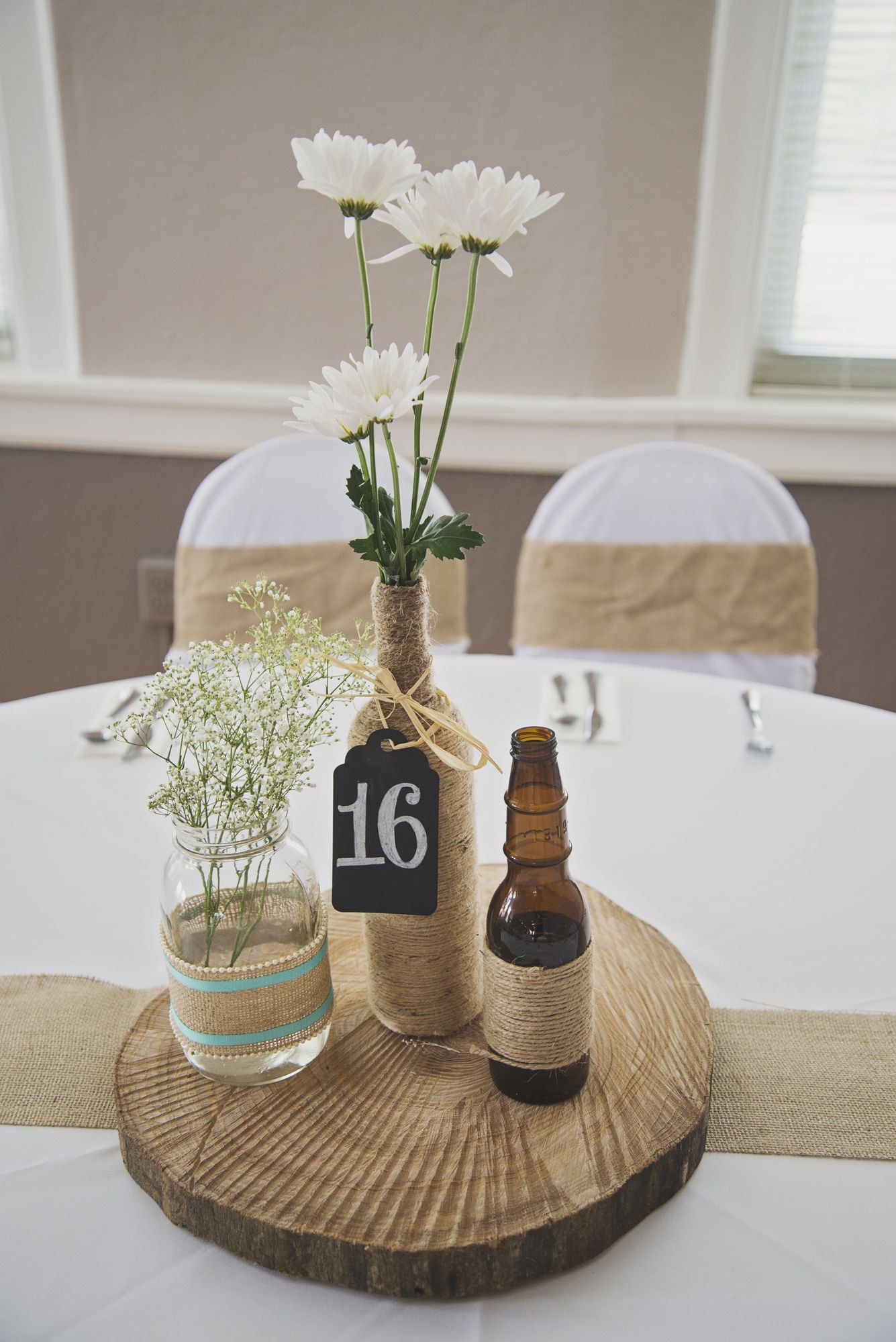 Rustic DIY Tree Stump Centerpieces with Twine-Wrapped Beer Bottles,  Daisies, and Baby's