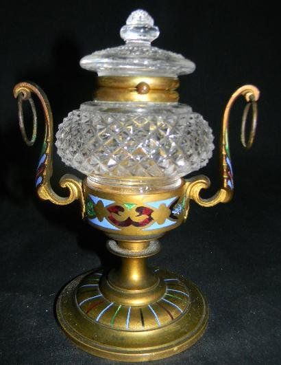 1880s CHAMPLEVE ENAMEL ORMOLU CUT GLASS INKWELL. PEDESTALED AND LEAF SCROLL HANDLED INKWELL STAND. THE ORMOLU BRASS IS WITH CHAMPLEVE ENAMELS ON THE BASS FOOT, THE COLLAR FOR THE INKWELL HOLDER, AND THE HANDLES. THE INKWELL WITH MOUNTED LID IS OF DIAMOND POINT PATTERN CUT GLASS. UNMARKED, PROBABLY FRENCH MADE.  ORIGINAL ORMOLU FINISH WITH SLIGHT PATINA.