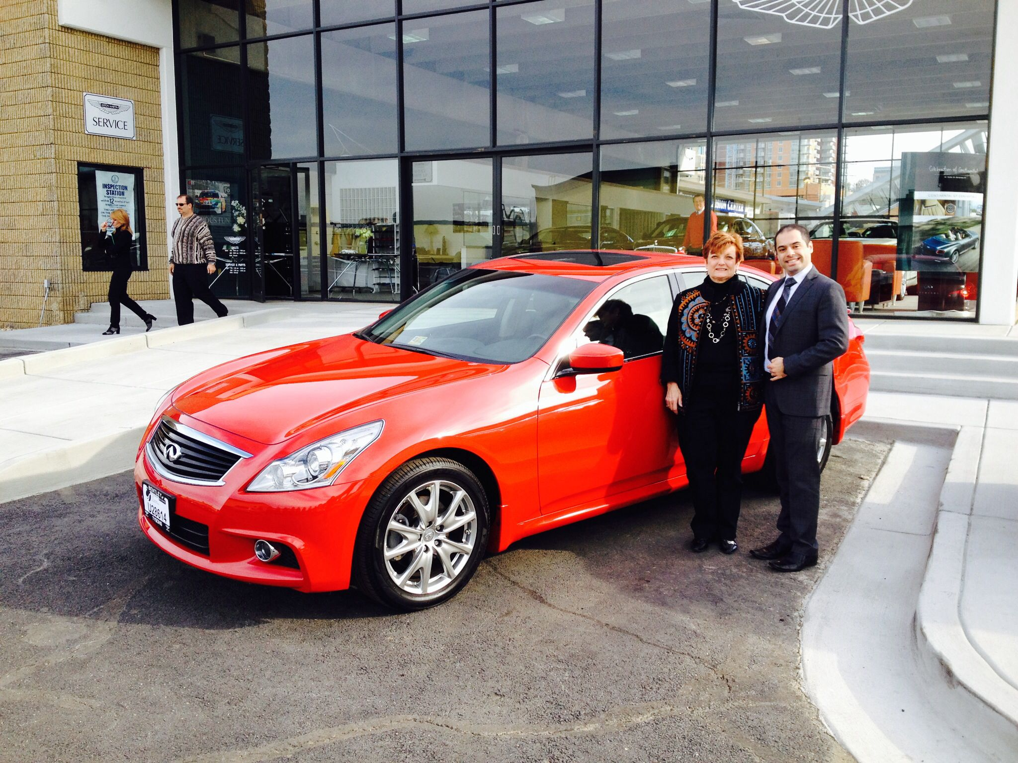 Mrs. Pizzano on left taking delivery of her first Infiniti