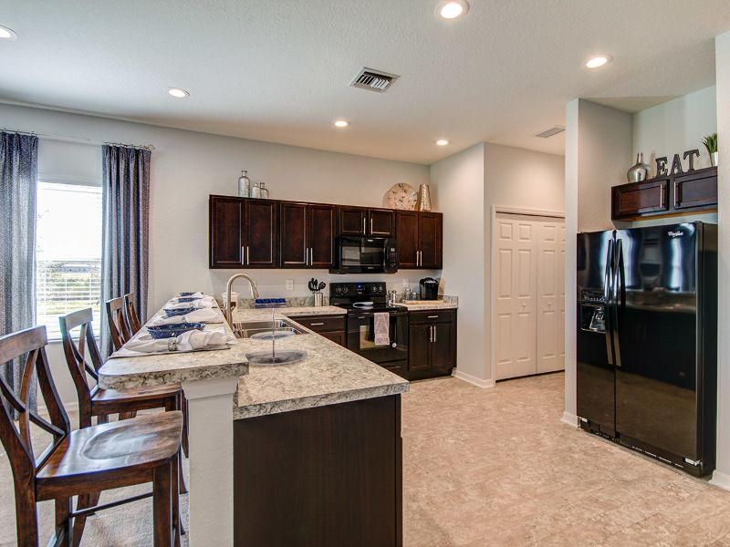 Dark Cabinets Light Counters And Flooring Dramatic Kitchen Design Highland Homes Model Home In Sarasota Flori With Images Highland Homes Stylish Kitchen Home Builders