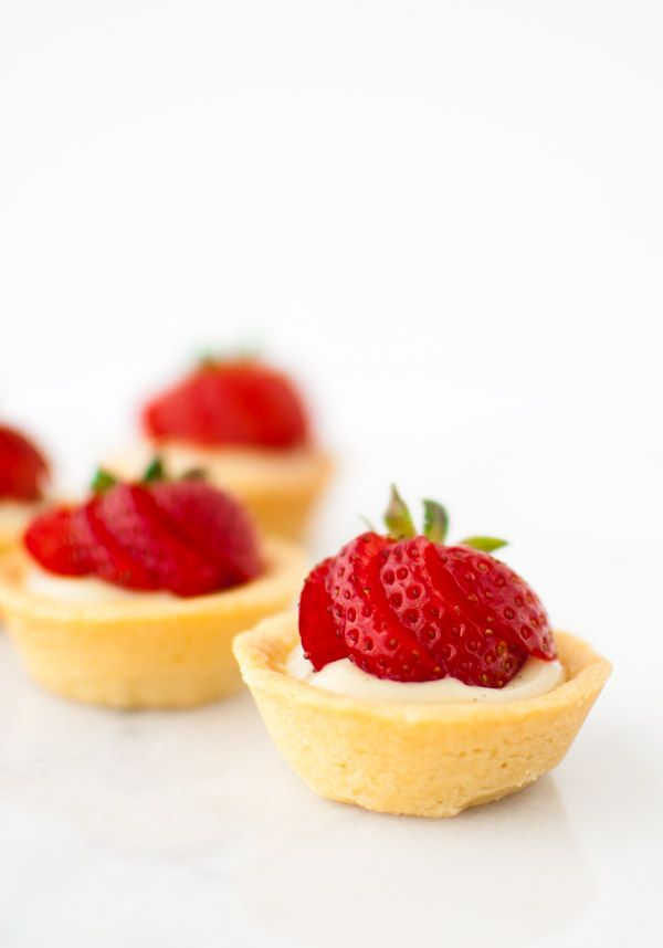 Strawberry Tartlets with Vanilla Pastry Cream - mini fruit tarts filled with vanilla pastry cream in a delicate cookie crust. | tamingofthespoon.com