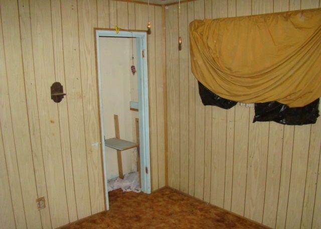 ugly dirty bedroom wood paneling plastic bags sheet in window