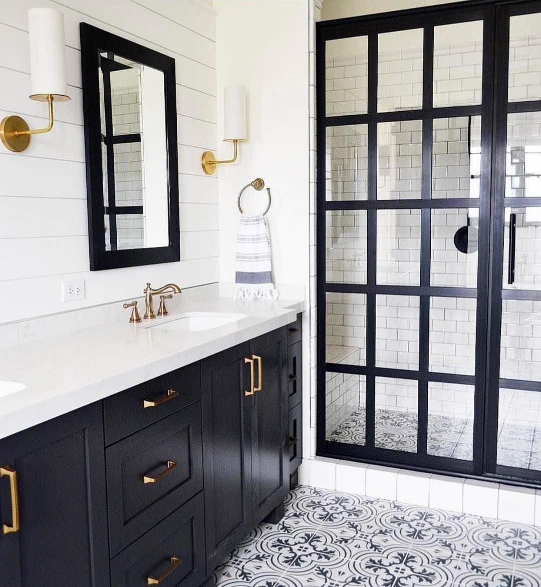 Modern Farmhouse Bathroom With Black Framed Shower Door Vanity Brass Fixtures Shiplap Paneled Wall And Cement Floor Tile Screen
