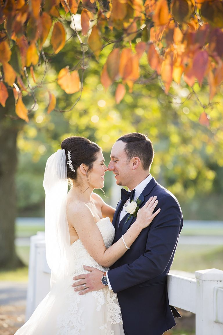 Bride and groom with autumn leaves at rose tree park by krista