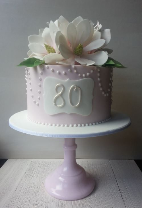 Pale pink cake with sugar magnolias for an 80th birthday.
