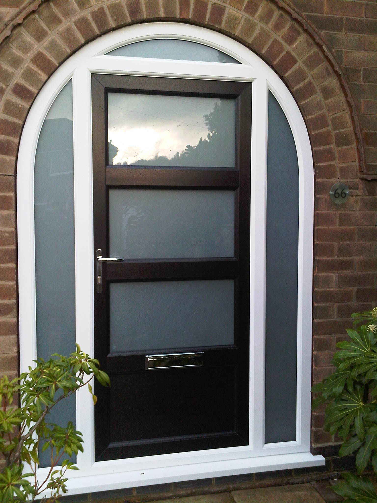 Bespoke UPVC door in black with arched top frame side panels