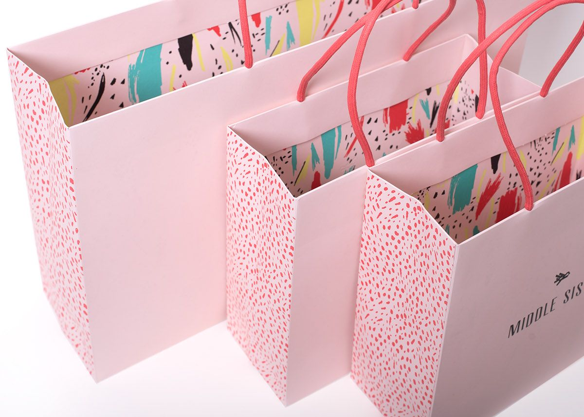 Packaging design for custom fashion retail shopping bag. Design of two unique sizes which showcase three unique custom patterns that we created for the program (exterior side gusset, internal bottom panel and interior wall graphics. Custom dip dyed ultra …