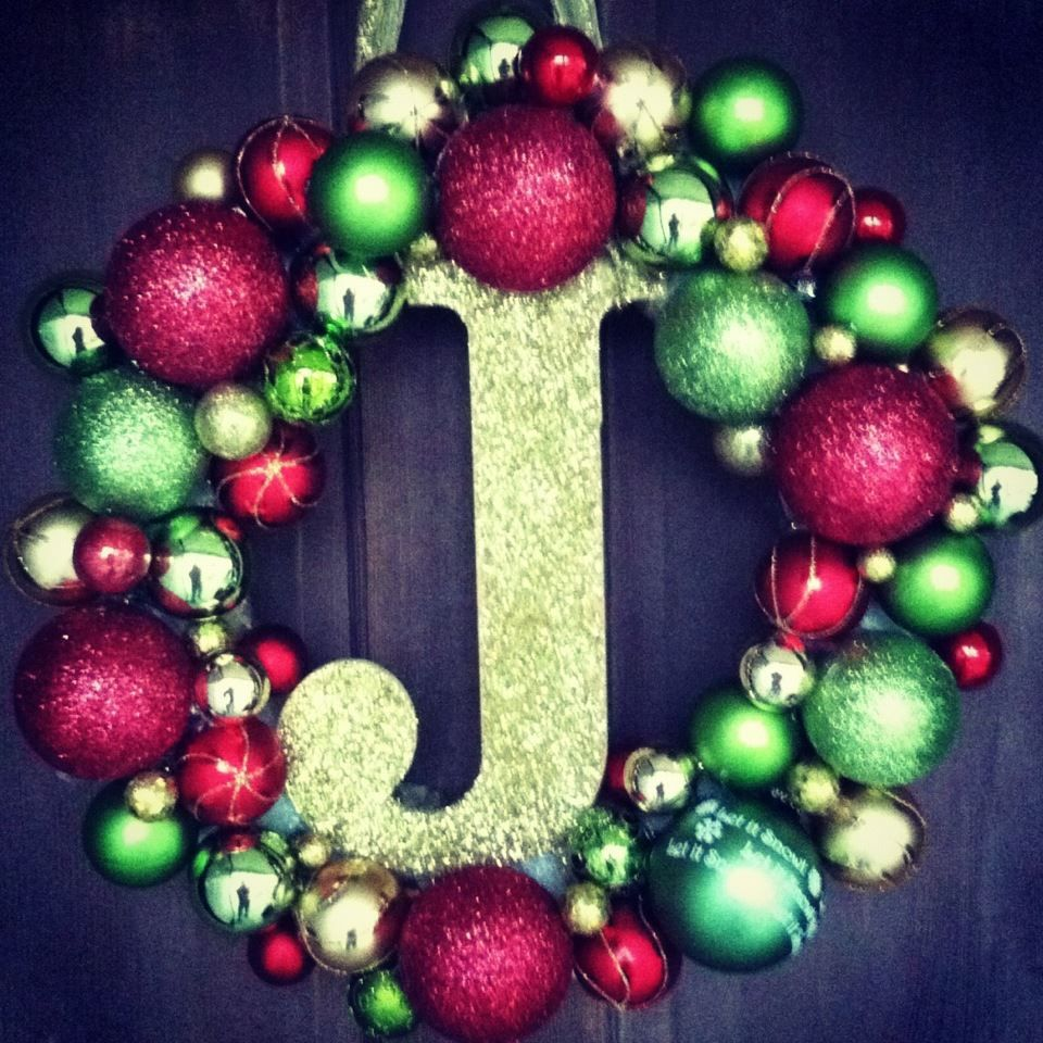 Ornaments, a styrofoam wreath, a glue gun, a wooden letter and glitter are