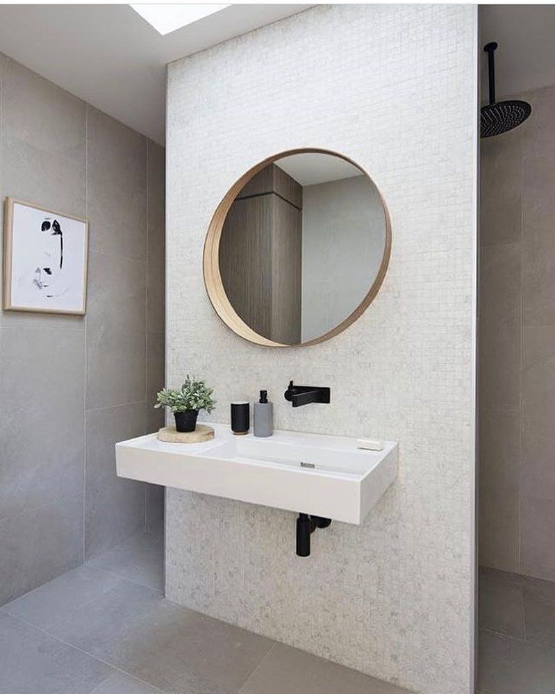 Square tiled wall, round wooden trimmed mirror, white floating basin ...