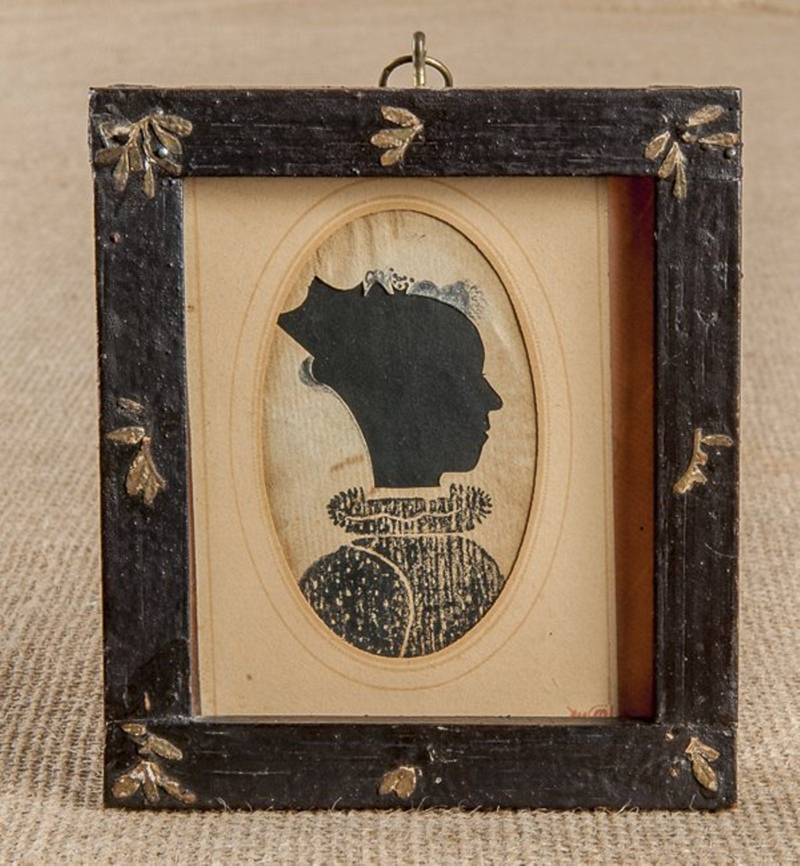 Hollowcut and stenciled silhouette of Augustia Wallace, Holland, Massachusetts, retaining an early decorated frame, 3 1/8'' x 2''. CONDITION Pencil inscription verso identifies sitter. Moderate staining. Provenance: The Collection of Glee Krueger, Needlework Scholar.