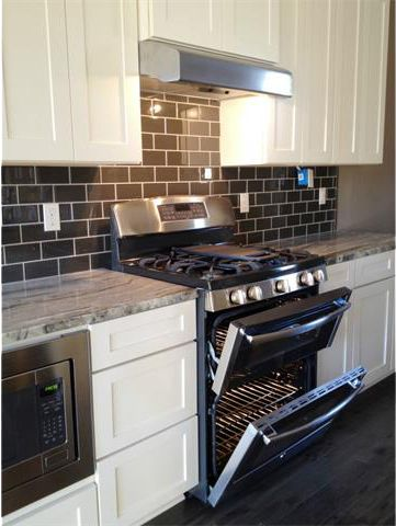Stainless steel gas range & built-in microwave with plenty of storage.
