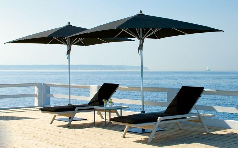 sombrillas y tumbonas negras en la terraza - Sombrillas De Terraza