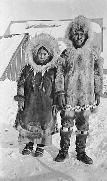 84a2dfa0e Eskimo couple wearing fur parkas and mukluks standing in snow with ...