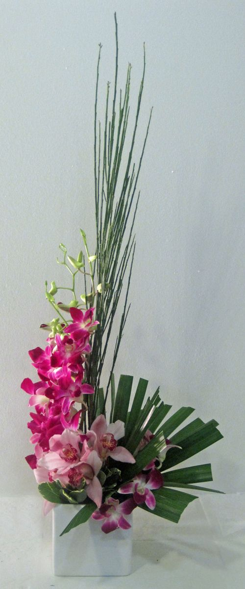 Modenr Centerpiece Idea Cymbidium And Dendrobium Orchids With Palms Reeds And Othe Orchid Arrangements Tropical Floral Arrangements White Flower Arrangements