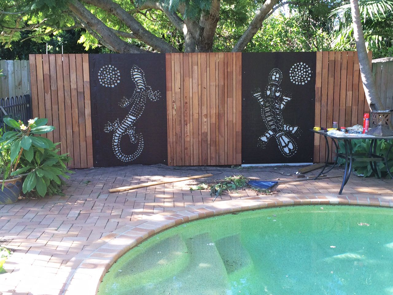 Decorative screens used as fence panels around a backyard for Pool privacy screen