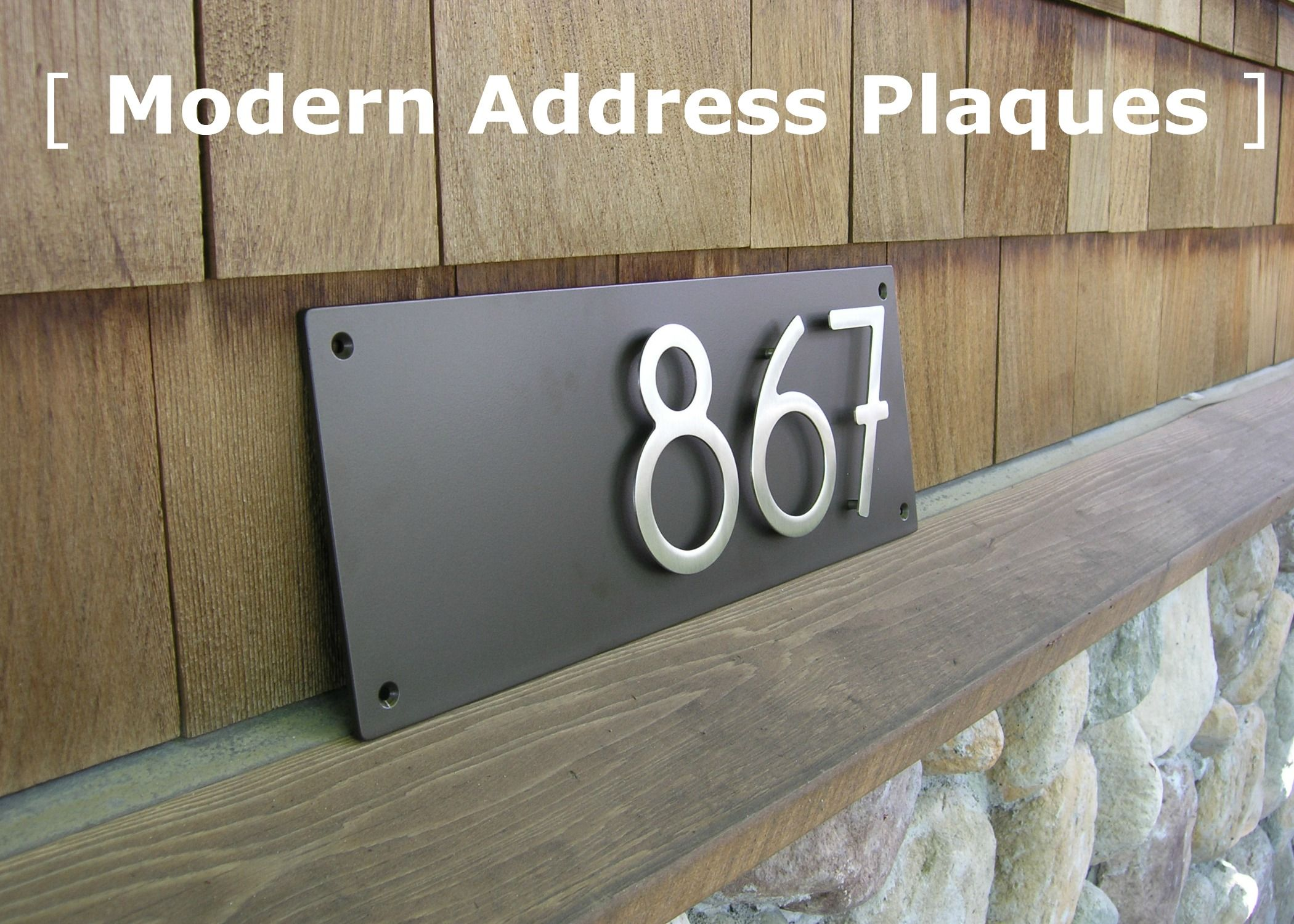 Modern address plaques with an offset alignment plaque measures 18 long x 7 high numbers are 5 high brushed stainless numbers on a dark bronze