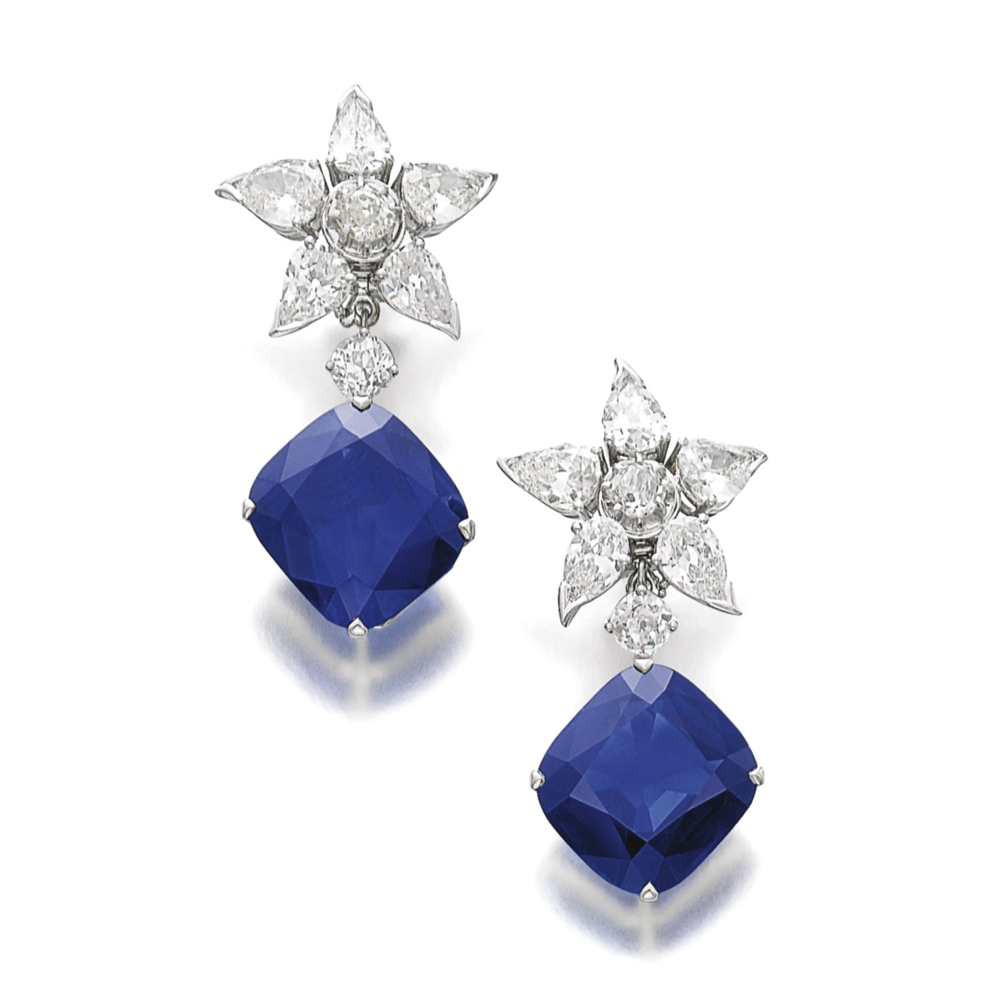 The Richelieu Sapphires, a pair of rare and magnificent sapphire and diamond earrings Each set with a cushion-shaped sapphire weighing 26.66 and 20.88 carats respectively, suspended from a star surmount set with a cushion- and pear-shaped diamonds, post and hinged back fittings.