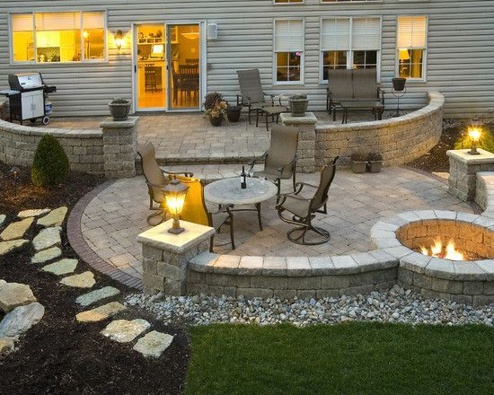 A Well Designed Front Yard Area With Fire Pit Made Of Natural Stones Lighting