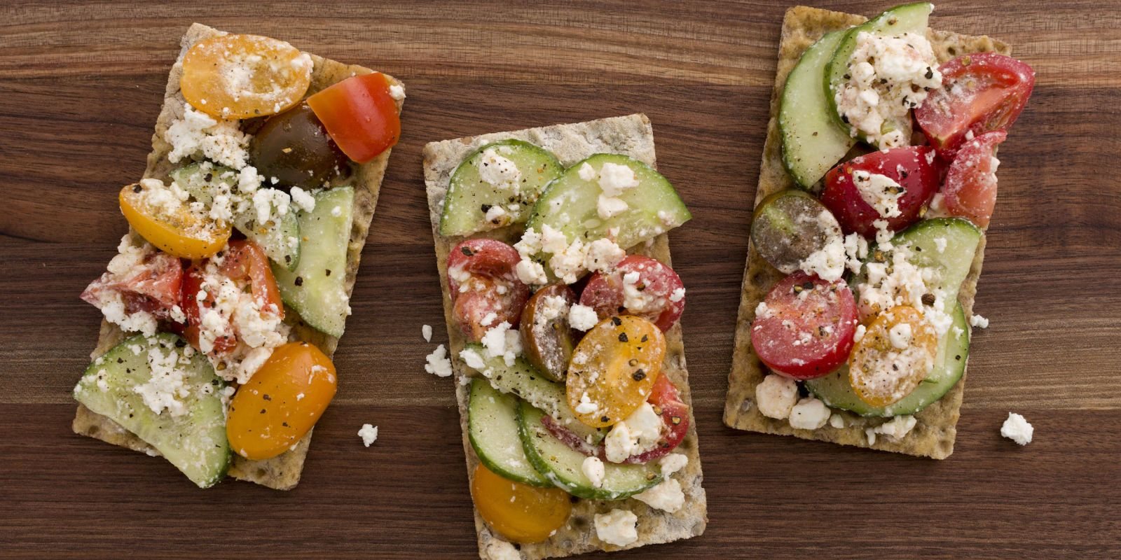 """Tomato and Feta """"Pizzas""""  Top multigrain crackers with a delicious feta-tomato-cucumber salad for a satisfying snack."""