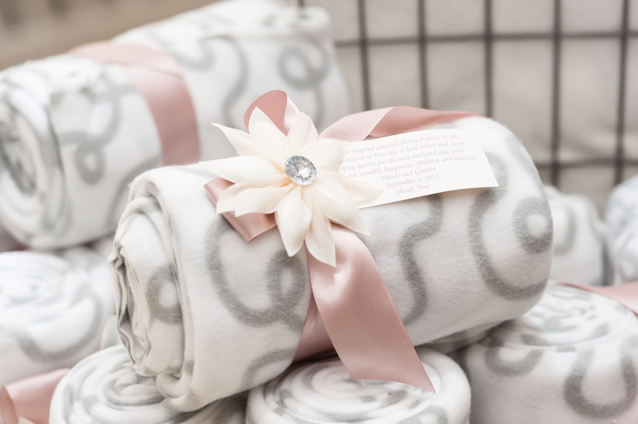 Wedding favours - Blankets tied in a blush ribbon accompanied with a ...