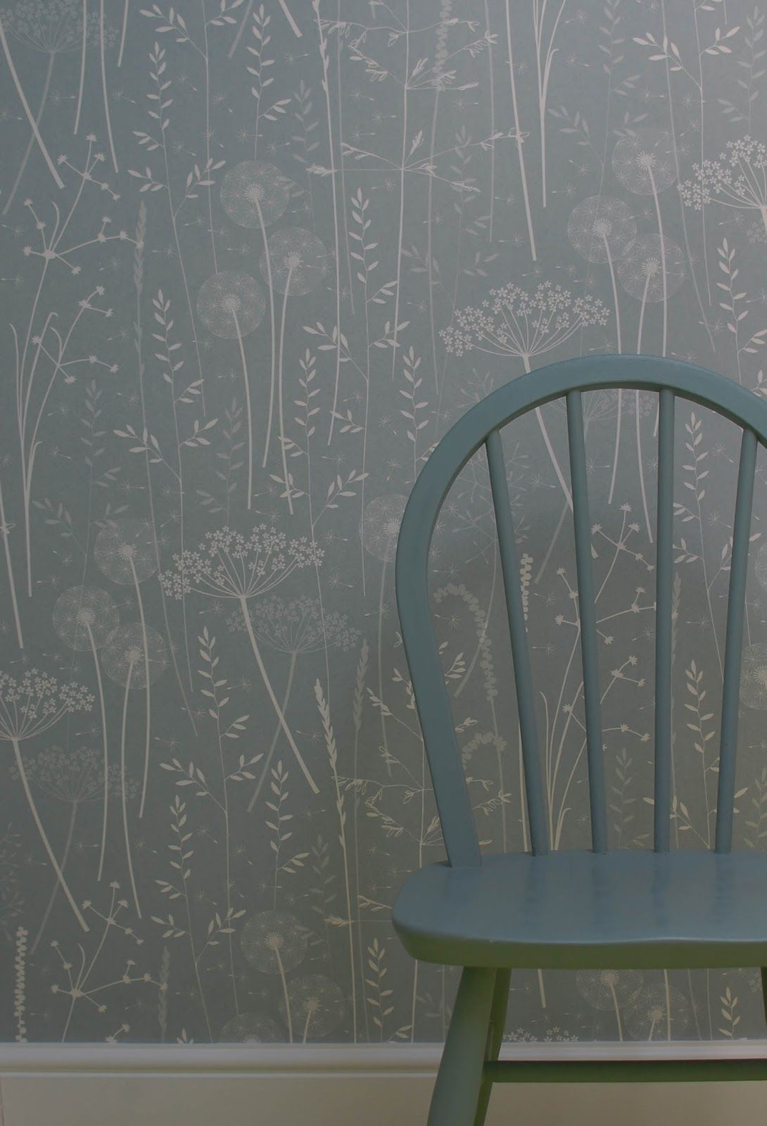 Paper Meadow wallpaper in teal - a quiet and gentle wallpaper design by Hannah Nunn featuring cow parsleys, dandelion clocks, grasses and seeds blowing in the wind.  Shown here at Elmet Farmhouse with a painted ercol chair.